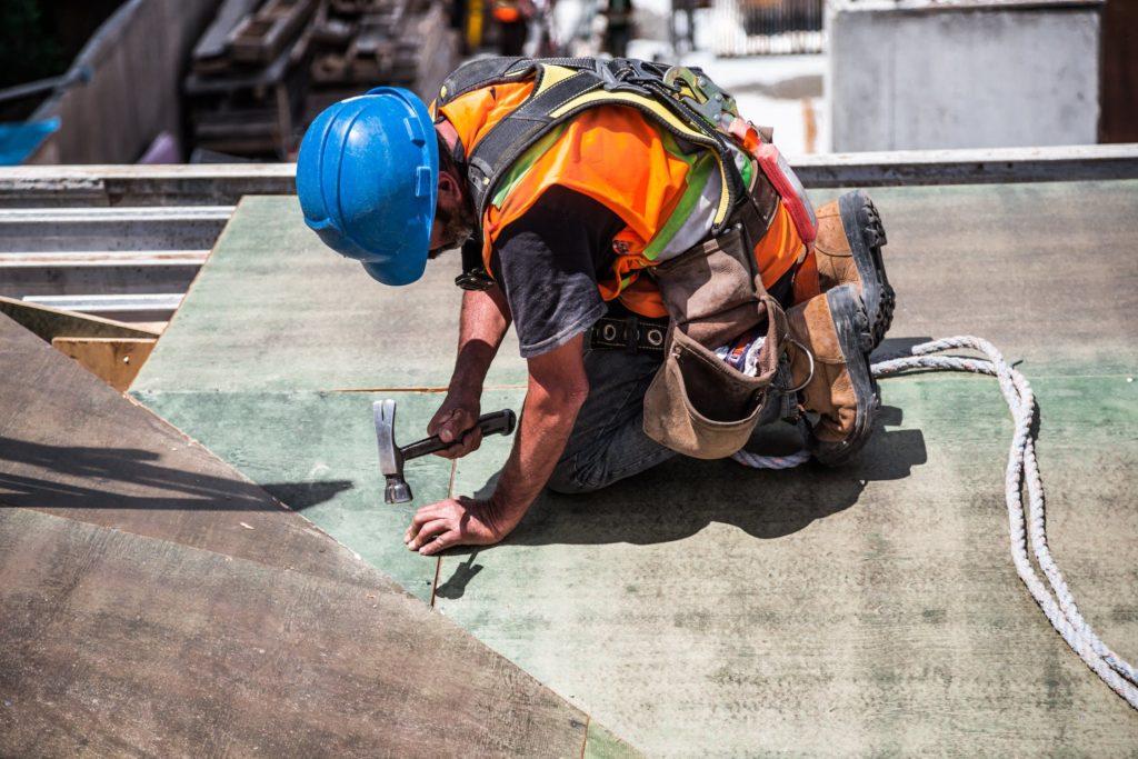 ouvrier marteau à genoux corde outils