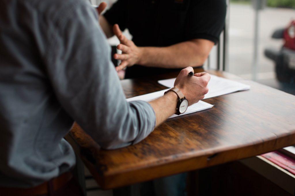 deux personnes papiers stylo montre discussion